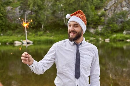 A young smiling businessman, wearing a Santa Claus hat, holds a burning sparkler in his hand, standing against a background of green trees and a river in the wild Foto de archivo - 133384151