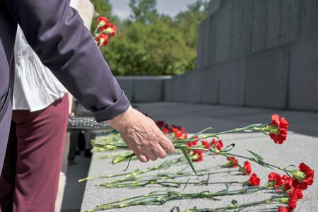 A hand puts red carnations on a granite gravestone. Memory of the dead Foto de archivo - 133384154