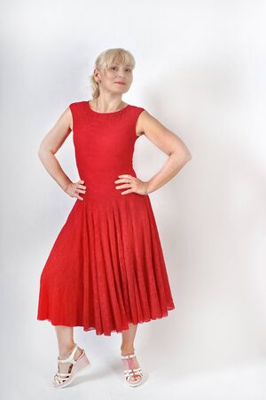 Pretty blonde fifty years old in a red dress dancing and smiling at the camera, isolated full length portrait Foto de archivo - 133384160