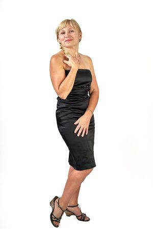 Pretty blonde fifty years old in a black dress with bare shoulders smiling at the camera, isolated full length portrait Foto de archivo - 133384161