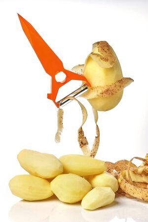 Peeled raw potato plays on an orange peeler rock like a guitar close-up