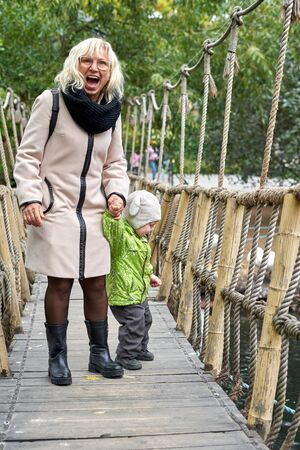 A woman in a coat and a little boy in overalls cross a suspension rope bridge, vertical frame Foto de archivo - 133384171