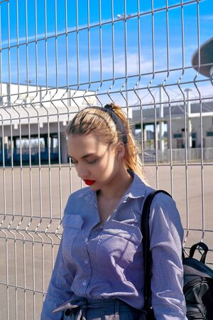 A beautiful girl is leaning against a lattice gate. Waiting for release, transfer to prison Foto de archivo - 133384174