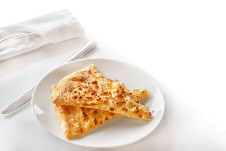 Two slices of delicious pizza on a white plate. Hot Khachapuri on a white plate. Khachapuri dish of Georgian cuisine Foto de archivo - 133384175