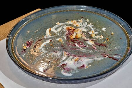 Cake crumbs and smeared cream on a flat blue dish, close-up. Eaten delicious dessert