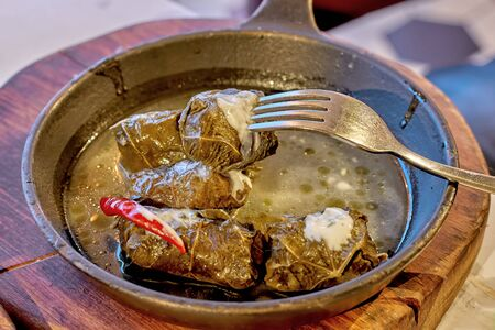 Delicious stuffed grape leaves (traditional doom Mediterranean cuisine Dolma) in a small skillet, wooden stand with a sauceboat and fork, side view close-up Foto de archivo - 133384615
