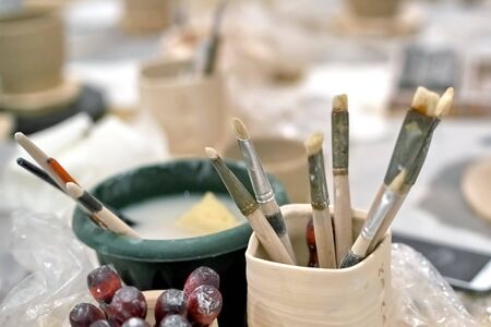 Fragment of an art workshop, old brushes in a wooden glass and brushes dipped in water Foto de archivo - 133473910