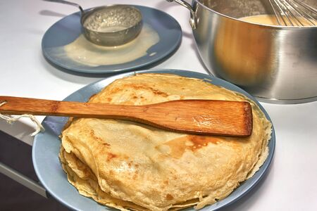 Cooking pancakes, Whisk in a pan with batter and a plate with hot pancakes, close-up Foto de archivo - 134547948