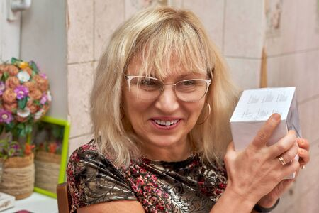An elderly pretty blonde in glasses holds a box with a gift in her hands, an emotion of joy and happiness Foto de archivo - 134547953