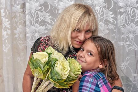 Granddaughter congratulates grandmother with flowers. Grandmother and granddaughter hugging smiling at camera Foto de archivo - 134547955