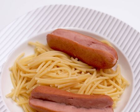 Notched sausages with pasta on a white plate close-up on a white background Foto de archivo - 134548446