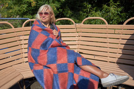 Blonde middle-aged wrapped a plaid blanket sitting on a wooden bench in Sunny day 免版税图像