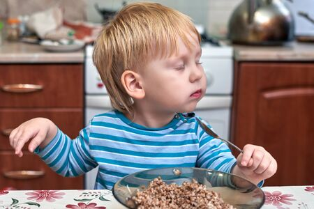 Three-year-old boy with red hair, eat Breakfast in the kitchen. Closing his eyes in pleasure. The emotions of a child for Breakfast 版權商用圖片