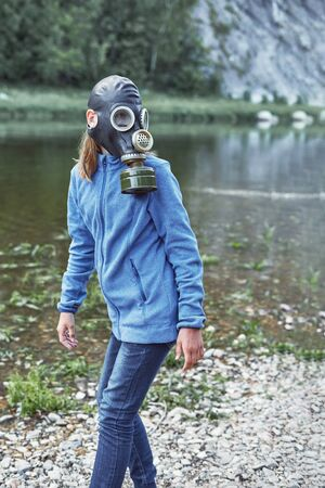 A girl of thirteen in a gas mask in a jacket and jeans turned to look at the background of a mountain river Banque d'images