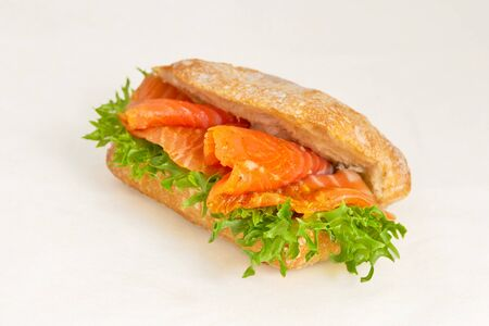 Sandwich with red fish salmon, Steelhead or trout and green salad leaves. Tasty and healthy fast food. Closeup on a light background, a diagonal frame