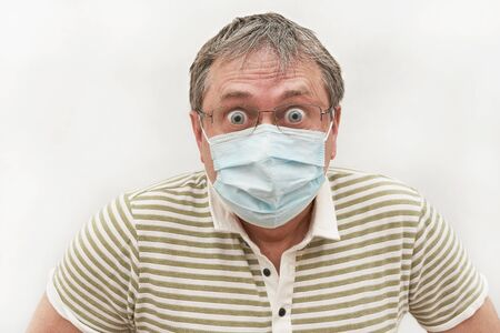 A man fifty years in a medical mask with glasses with bulging eyes. Emotion surprise and fear. Portrait on a light background