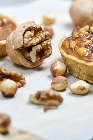 Round brown cake basket with milk filling. Still life with walnuts on the wooden boards. Vertical shot, close-up