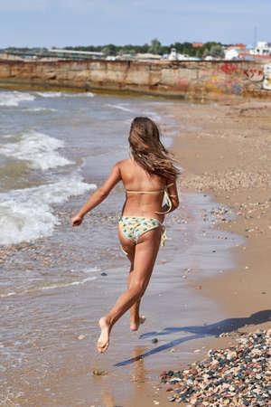 A teenage girl in a swimsuit runs along the beach along the sea. Back view