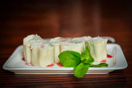White dish with japanese fruit dessert minari and green mint leaf on wooden table background Reklamní fotografie