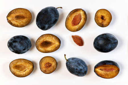 Ripe dark plums in various forms. Prunes on a light background, top view