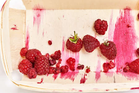 The half-eaten remnants of ripe raspberries in a small wooden container with streaks of red juice. Top view close up Reklamní fotografie