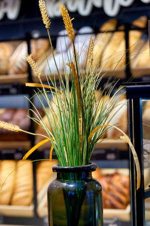 Spikelets of ripe wheat in a glass jar on a blurred background of shelves with bread in a bakery. Vertical frame Reklamní fotografie