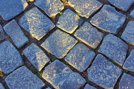 Fragment of an old road from square blocks. Granite pavement close up