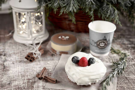 A cake decorated with blackberries and raspberries on a New Year table with a flashlight and a spruce branch. Frame toning