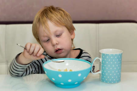 The child looks at the fork which he eats from the plate while sitting at the dinner table