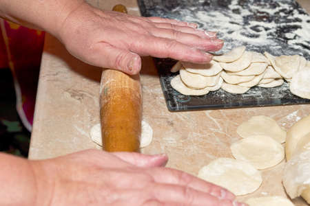 Hands with a wooden rolling pin roll out the dough on the kitchen table for making dumplings