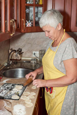 Senora, with a wooden rolling pin in her hand and in a yellow apron, prepares food in the kitchen. Vertical shot