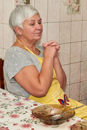 An elderly woman sits at a table with her hands folded in front of an empty plate. Grandma prays before dinner