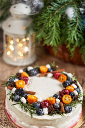 A large round cake decorated with fruits on a Christmas table with a lantern and a spruce branch. Vertical frame Reklamní fotografie