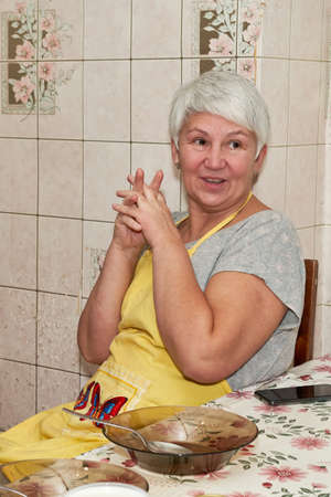 A grandmother with gray hair is smiling while sitting in front of an empty plate. The joy before dinner