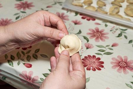 Hands soiled with flour hold a raw dumpling. Cooking homemade dumplings