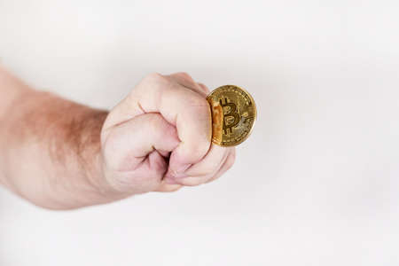 Bitcoin in the form of a round coin in a man hand in the form of a fig