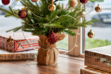 Fragment of a Christmas tree with toys and boxes with gifts on the windowsill overlooking the street