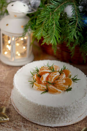 A large round cake decorated with tangerine slices on a New Year table with a flashlight and a spruce branch. Vertical frame Reklamní fotografie
