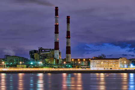 High factory chimneys on the Sinopskaya embankment of the Neva River. Russia, Saint Petersburg, night city landscape