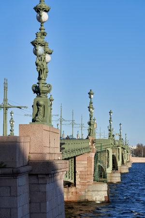 Fragment of the Trinity Bridge with ancient lanterns across the Neva River. Russia, Saint Petersburg cityscape, vertical shot Reklamní fotografie