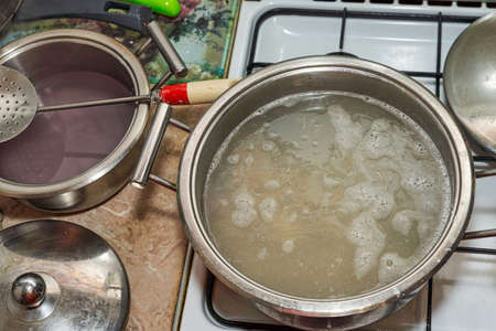 A large saucepan of simmering broth on a white stovetop. View from above