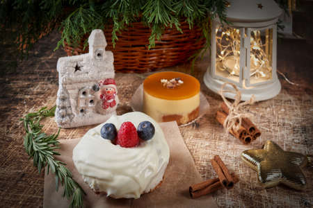 A cake decorated with blackberries and raspberries on a New Years table with a flashlight and a spruce branch. Christmas Reklamní fotografie