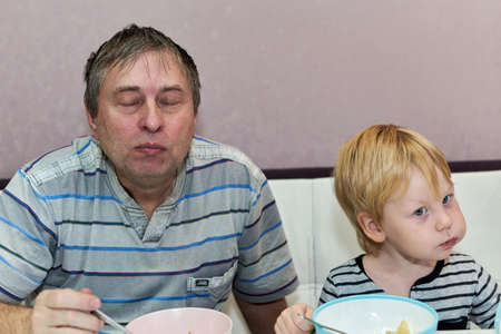 A man with closed eyes and a child with a full mouth are sitting at the table
