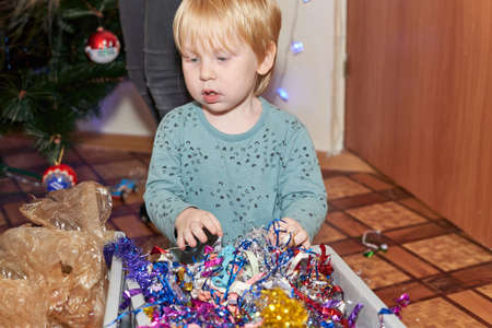 Little boy with blond hair sits in front of a box of shiny tinsel for the christmas tree