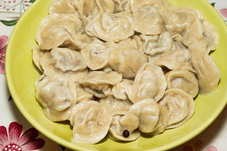 Cooked dumplings in a green plate on the dining table. Close up Reklamní fotografie