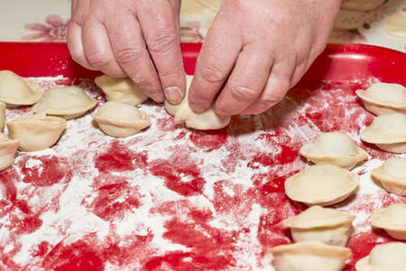 A hand is placing raw dumplings on a red floured tray. Cooking at home Reklamní fotografie