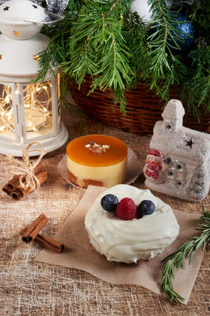 A cake decorated with blackberries and raspberries on a Christmas table with a flashlight and a spruce branch. Vertical frame
