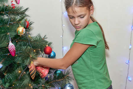 Teenage girl takes off toys from artificial christmas tree