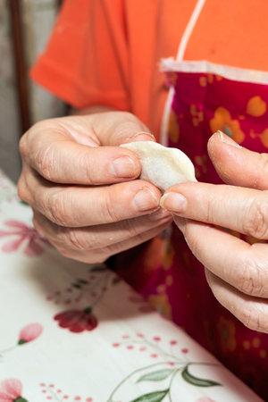 Hands soiled with flour hold a raw dumpling. Cooking homemade dumplings. Vertical shot Reklamní fotografie