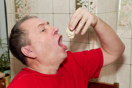 A man in the kitchen puts himself a dumpling with his hand in a wide open mouth Reklamní fotografie